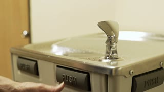 businesswoman at a office drinking fountain getting water 4k