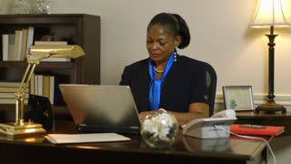businesswoman corporate CEO working at her desk answers phone