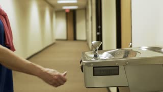 businesswoman getting a drink of water from a drinking fountain 4k