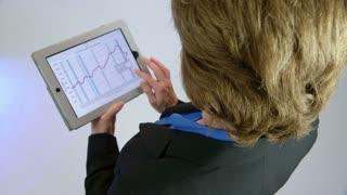 businesswoman looking at a tablet pc turns and smiles at camera