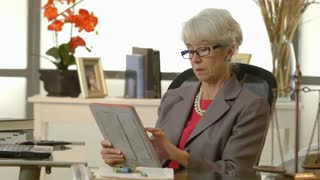 businesswoman or lawyer checking her tablet pc in her office