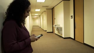 Pretty Hispanic millennial waiting in corporate office building hallway staying in touch via her smartphone.