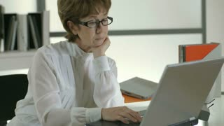 businesswoman thinking and typing on a laptop