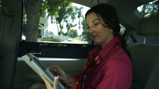 businesswoman using a tablet pc in a car.