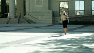 businesswoman walking past a downtown building