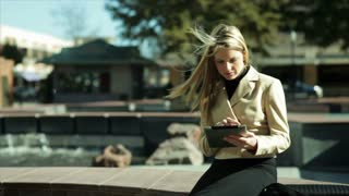 businesswoman with tablet sitting by a fountain