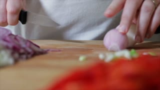 chef cuts a red onion
