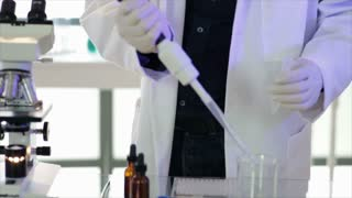 Chemist using a pipette to collect a sample