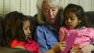 Children showing grandmother something on the tablet pc