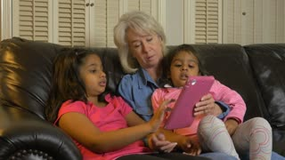 Children showing their grandmother something on a tablet pc