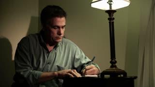 close man writing at a small desk
