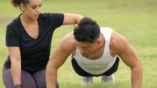 close shot woman helping her male friend do pushups outdoor