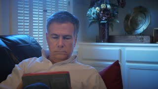 closeup man reclining on his couch using an electronic tablet 4k