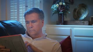 closeup man reclining on his couch using an electronic tablet smiles at camera 4k