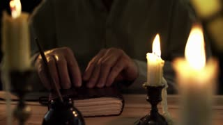 closeup of 1830 man writing in his diary by candlelight 4k