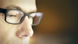 closeup of a man wearing glasses looking at a computer screen 4k
