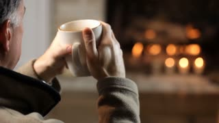 closeup of man drinking coffee in front of fireplace