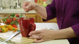 closeup of mature woman making tea