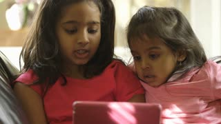 closeup of two cute little girls looking at a tablet pc