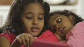 closeup of two Indian children looking at a tablet pc