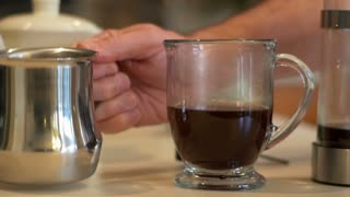 closeup pouring milk in the coffee mug slow motion