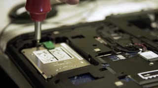 computer tech removing a hard drive from a laptop 4k