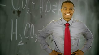 confident teacher in front of chalk board