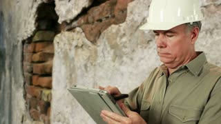 Construction worker on phone and using a tablet pc