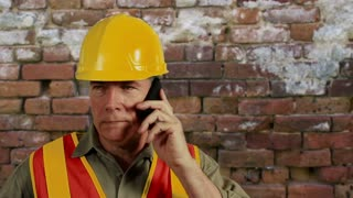 Construction worker using a cell phone