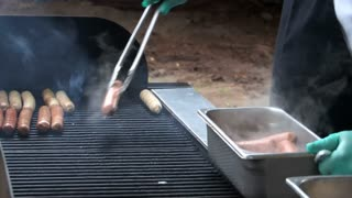 cook placing sausages on a grill.