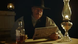 cowboy reading newspaper pulls out gun