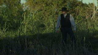 cowboy walks in scene.