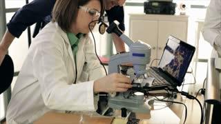 CSI team looking at evidence on microscope
