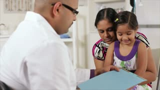Curious little girl asking the doctor about her chart