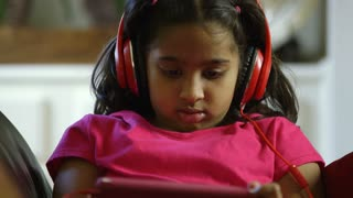 cute Indian girl listening to her headphones looks up and smiles