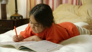 cute little girl coloring while laying in bed