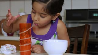 Cute little girl drinking juice and eating