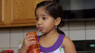Cute little girl drinking juice