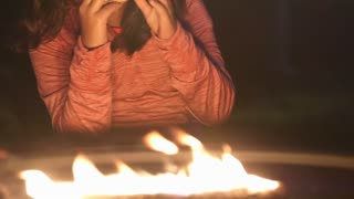 cute little girl eating a smore by a campfire