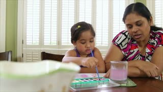 Cute little girl painting with her mother
