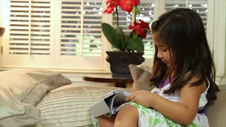 Cute little girl using a tablet pc looks up and smiles