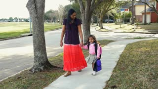 Cute little girl walking home from school with her mom slow motion