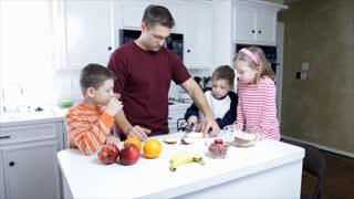 dad and kids eating fruit wide shot