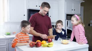 dad cutting fruit with his kids