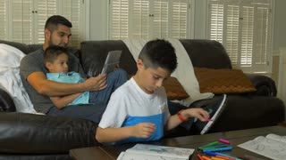 dad showing son tablet pc while other boy colors