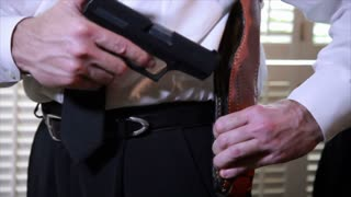 detective putting gun in holster