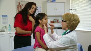 doctor checking the childs sore throat