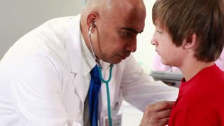 Doctor checking the lungs and breathing of a young male patient.
