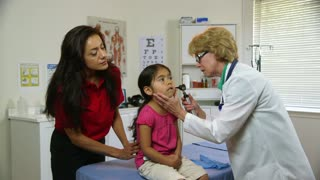 doctor checking the sick childs ears.