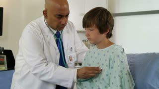 Doctor listens carefully to breathing and heart of boy patient.